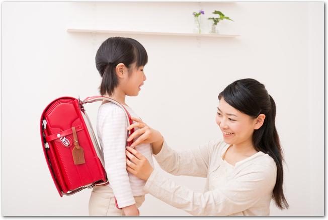 ランドセルを開いて準備をしている女の子とママ