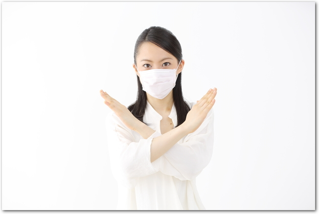 マスクをして手でバツ印をする女性