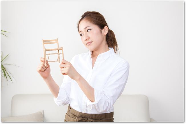 家具のミニチュアを手にイメージ作りをする女性
