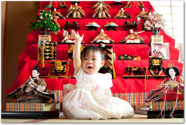 ひな段の前でかわいいドレスを着た赤ちゃん
