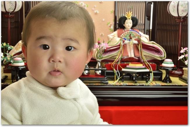 ひな段の前で笑顔の赤ちゃん