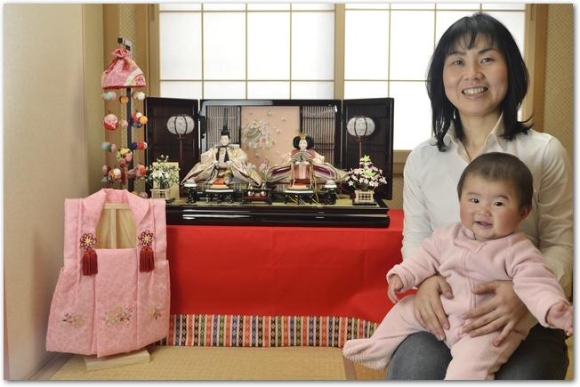 ひな飾りの前で笑顔のママと赤ちゃん