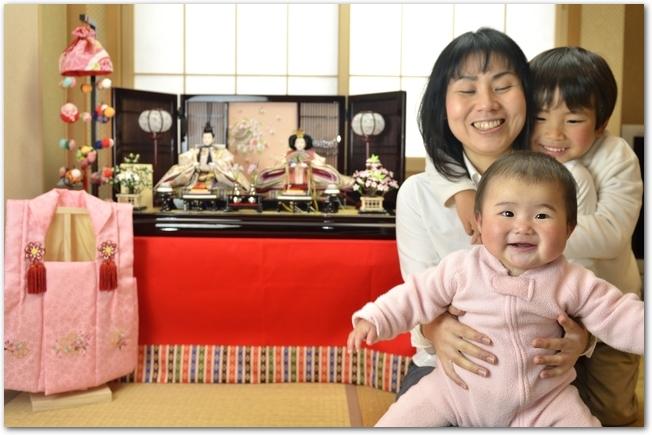 ひな飾りの前で記念撮影するママとお兄ちゃんと赤ちゃん