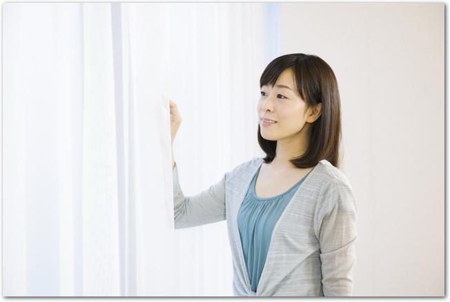 カーテンを開けて外を見る女性