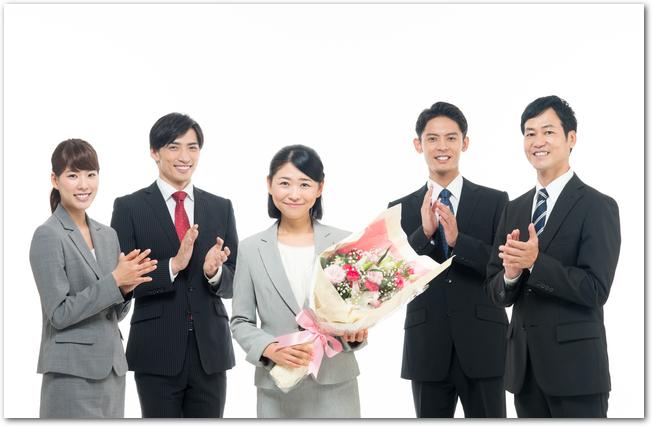 同僚から花束をもらう女性