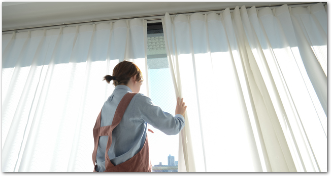 カーテン越しに外を見ている女性