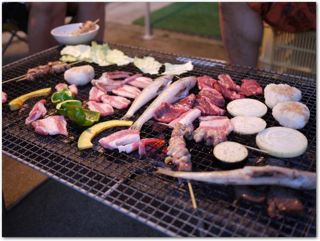 野菜や肉がいっぱいのったバーベキューの網