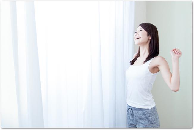 カーテンの横で気持ちよさそうに深呼吸する女性