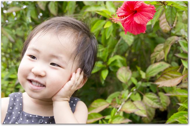 旅行先でお花をバックに記念撮影する女の赤ちゃん