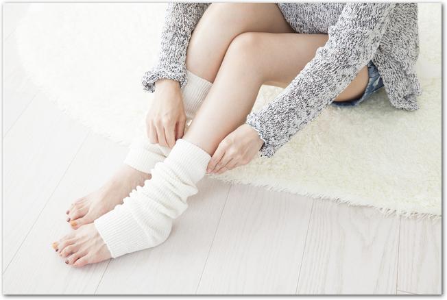 レッグウォーマーで足を温める女性