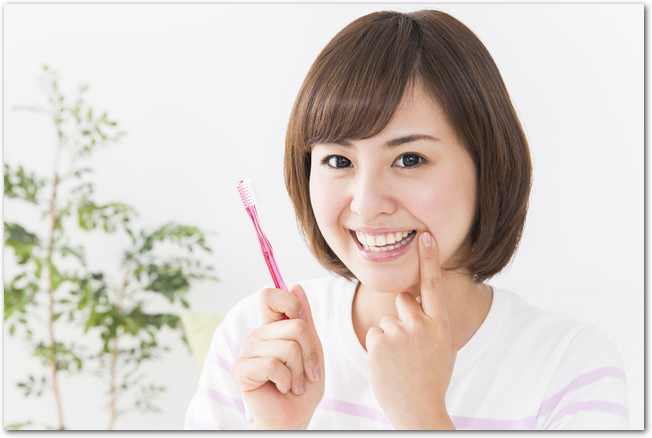 歯ブラシを持って笑顔の女性