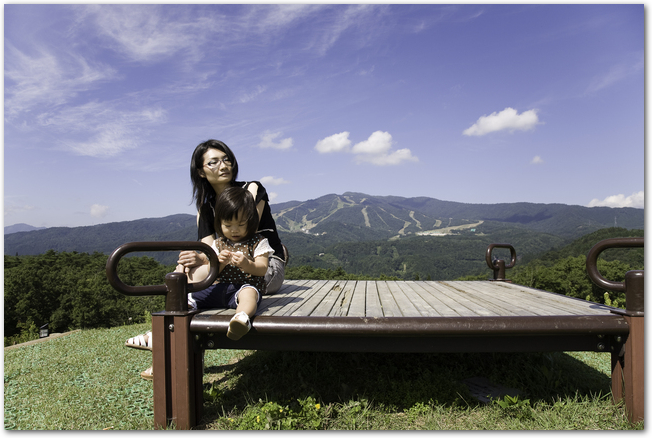 夏のスキー場を背景に自然を満喫するママと子ども