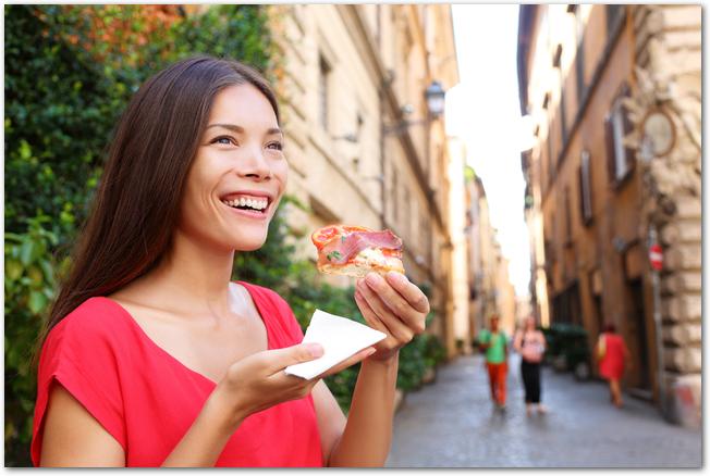 お祭りの屋台で軽食を買って食べる女性