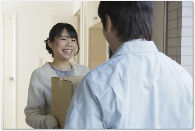 玄関先で宅配便を受取る笑顔の女性