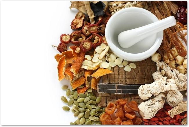 色々な漢方薬と白い陶器の乳鉢