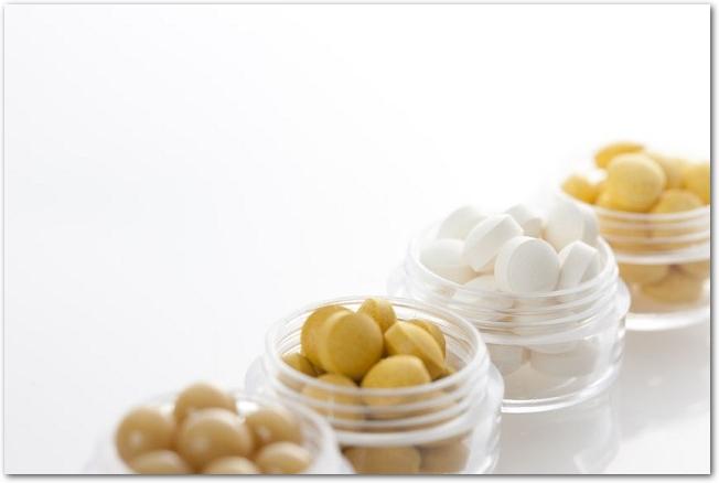 透明なケースに入っている黄色や白のサプリメントの錠剤