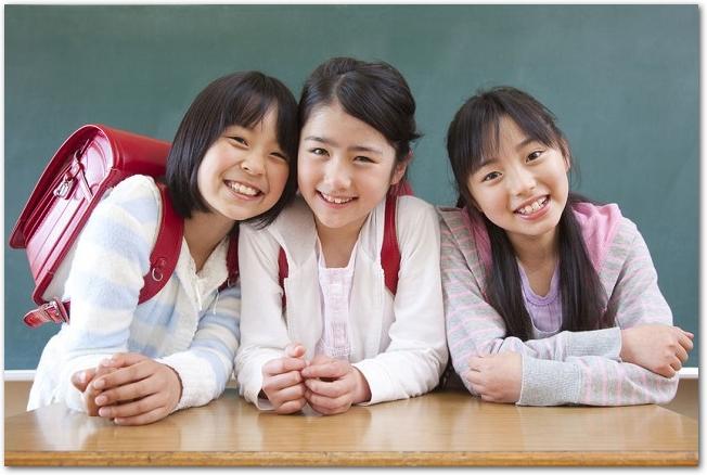 黒板の前で笑う3人の女子小学生