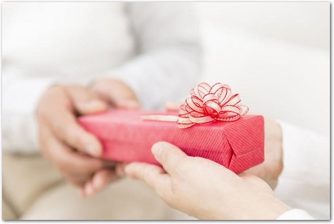 赤いプレゼントの箱を渡している手元の様子