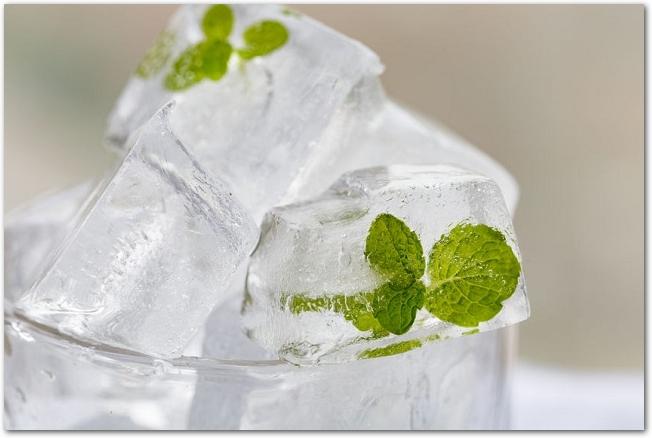 ミントの葉を入れて凍らせた氷がグラスに入れられている様子