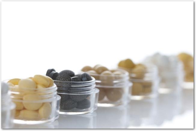 小さい透明な容器に入った様々なサプリメントが一列に並べられている様子