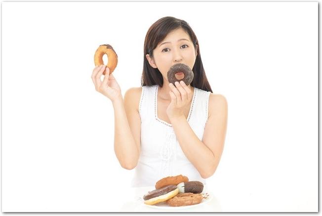 両手にドーナツを持って食べる女性の様子