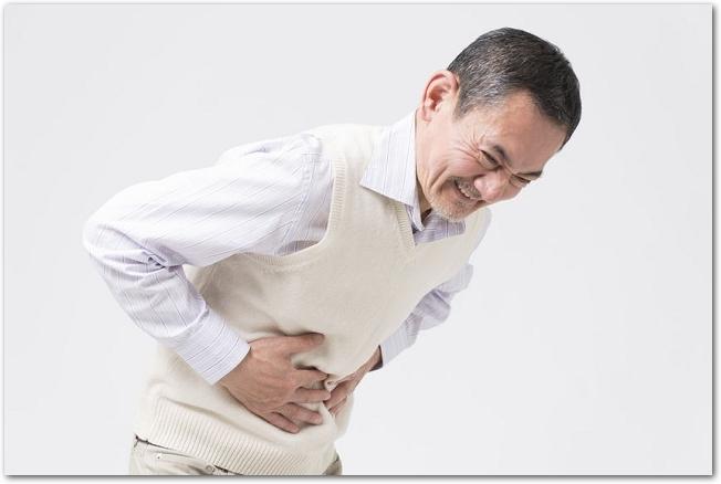 腹痛でお腹を押さえるシニア男性の様子