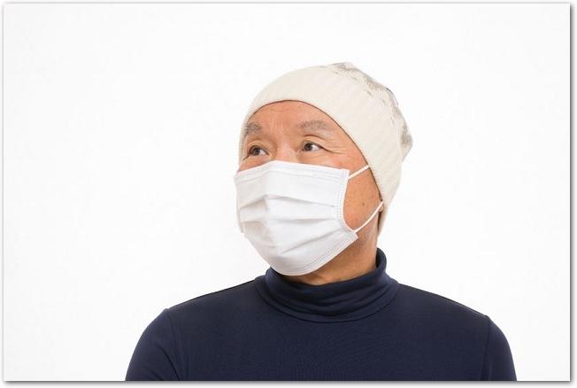 ニット帽をかぶってマスクをかけているシニア男性