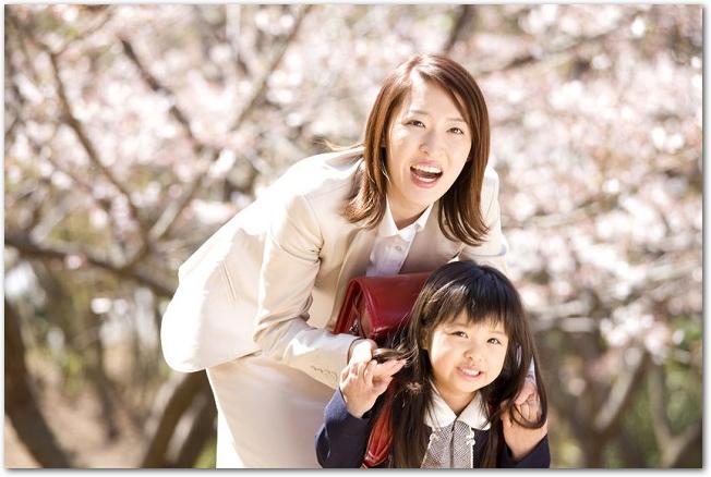 入学式の日に桜の木の下にいる笑顔の母娘の様子
