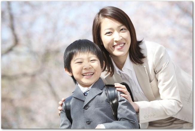 桜の木の下にいる笑顔の小学生の男の子と母親