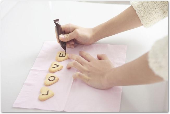 チョコペンでクッキーにLOVEと書いている女性の手元の様子