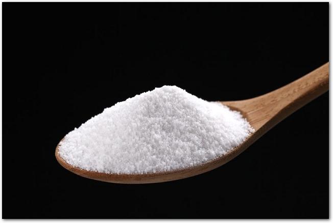 木のスプーンに塩が山盛りになっている様子