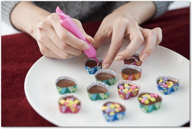 手作りチョコにピンクのチョコペンで文字を書こうとしている手元の様子