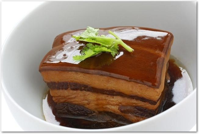 薬味の乗った豚の角煮が白皿に盛りつけられている様子