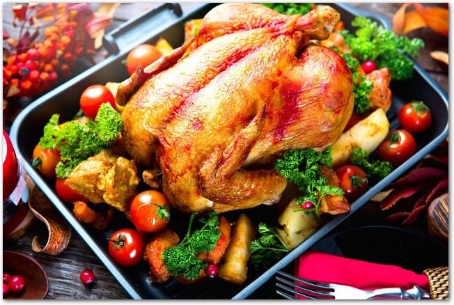 オーブンで焼かれた鶏の丸焼きの周りに野菜が盛りつけられている様子