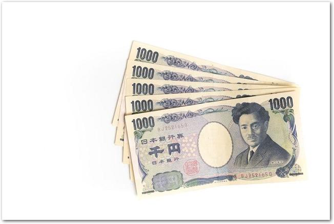 白背景に置かれた5枚の千円札