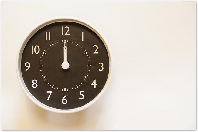 黒い文字盤の壁掛け時計が12時を指している様子