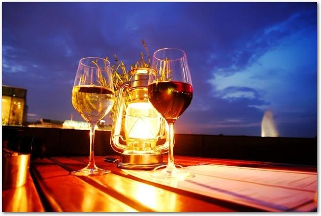 テーブルの上に明かりの灯ったランタンとワイングラスが2つ置かれている様子