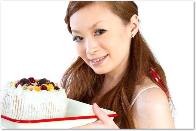 ホーローのバットに乗せたケーキを持つ女性の様子