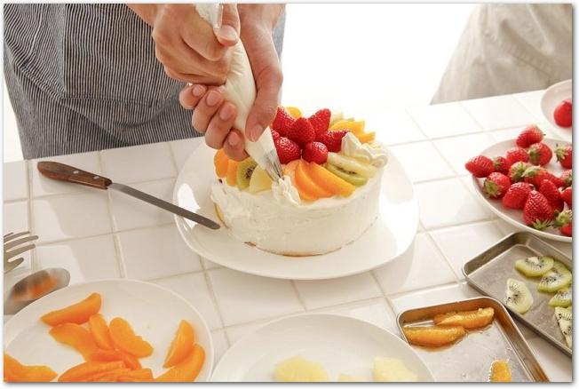 ケーキを生クリームとフルーツでデコレーションしている様子