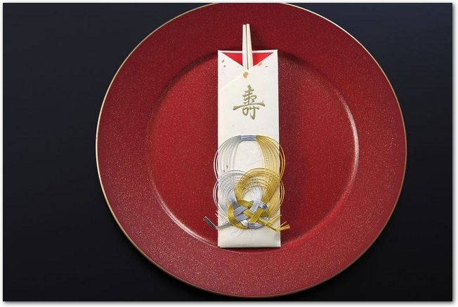 赤いお皿の上に祝箸が置いてある様子