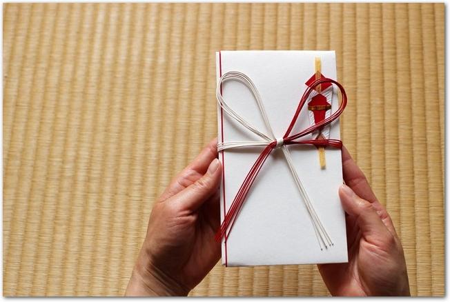 畳をバックに紅白の蝶結びの水引のついたご祝儀袋を持つ手元の様子